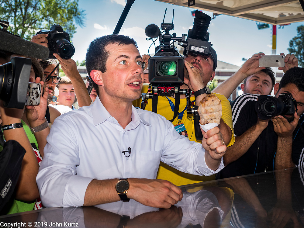 """13 AUGUST 2019 - DES MOINES, IOWA: PETE BUTTIGIEG with the """"pork chop on a stick"""" he bought at the Iowa State Fair. Buttigieg, the Mayor of South Bend, Indiana, is running to be the Democratic nominee for the US presidency. He spoke at the Des Moines Register Political Soap Box at the Iowa State Fair and then toured the fairgrounds. Iowa has the first event of the presidential selection cycle. The Iowa Caucuses are February 3, 2020.               PHOTO BY JACK KURTZ"""