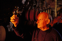Wine maker RÈnÈ Dauvissat observing the color of a glass of Chablis taken from his oak barrels in his cellar - Chablis, Burgundy.  Dauvissat's Chablis are considered among the best.