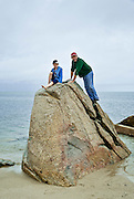 Dad and daughter climb beach boulder, Cape Cod, Massachusetts, USA