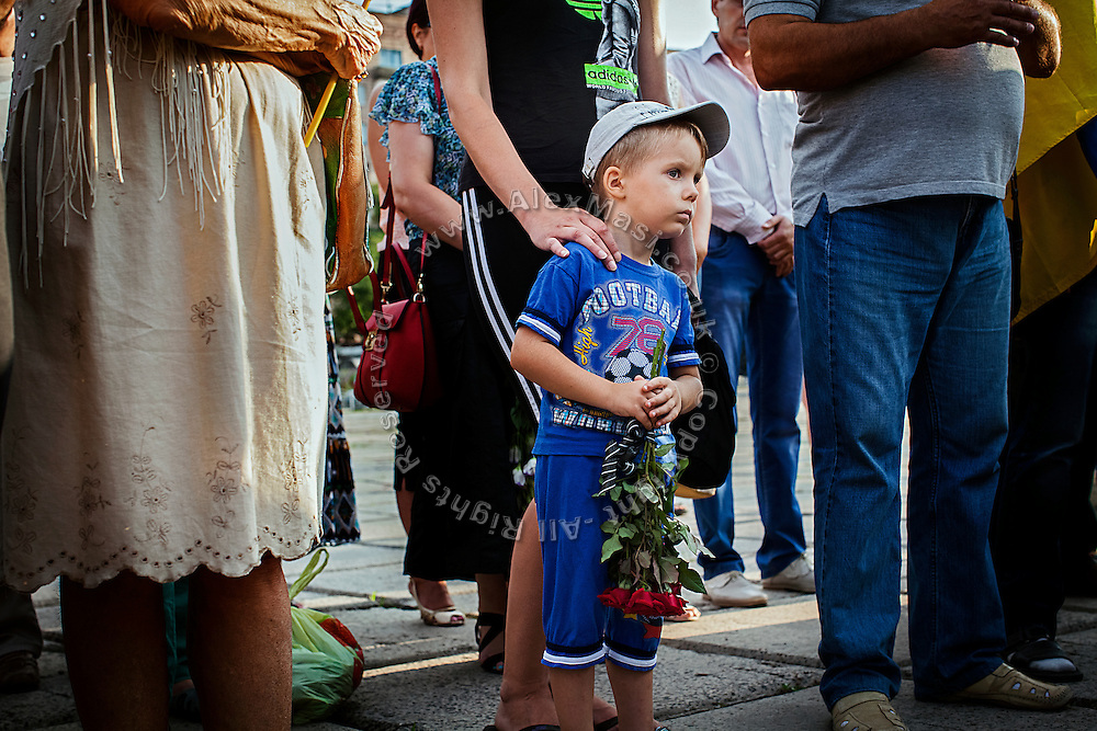 A boy holding roses is standing curious alongside Ukrainian patriots, military men and members of the clergy while attending a ceremony to commemorate recently killed soldiers during the Donbas war, in Mariupol, southeast Ukraine.