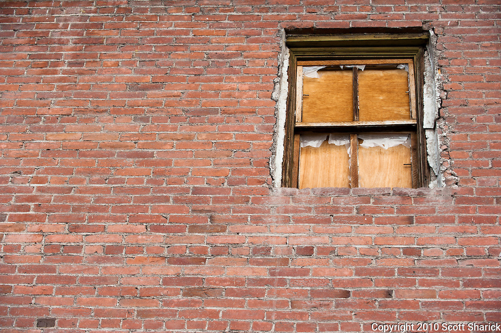 A brick wall with a broken window that is blocked by wood. Missoula Photographer