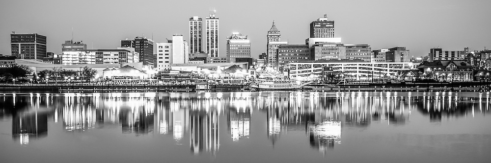 Peoria Illinois skyline at night panorama black and white photo of downtown Peoria city buildings reflection on the Illinois River. Panoramic picture ratio is 1:3.