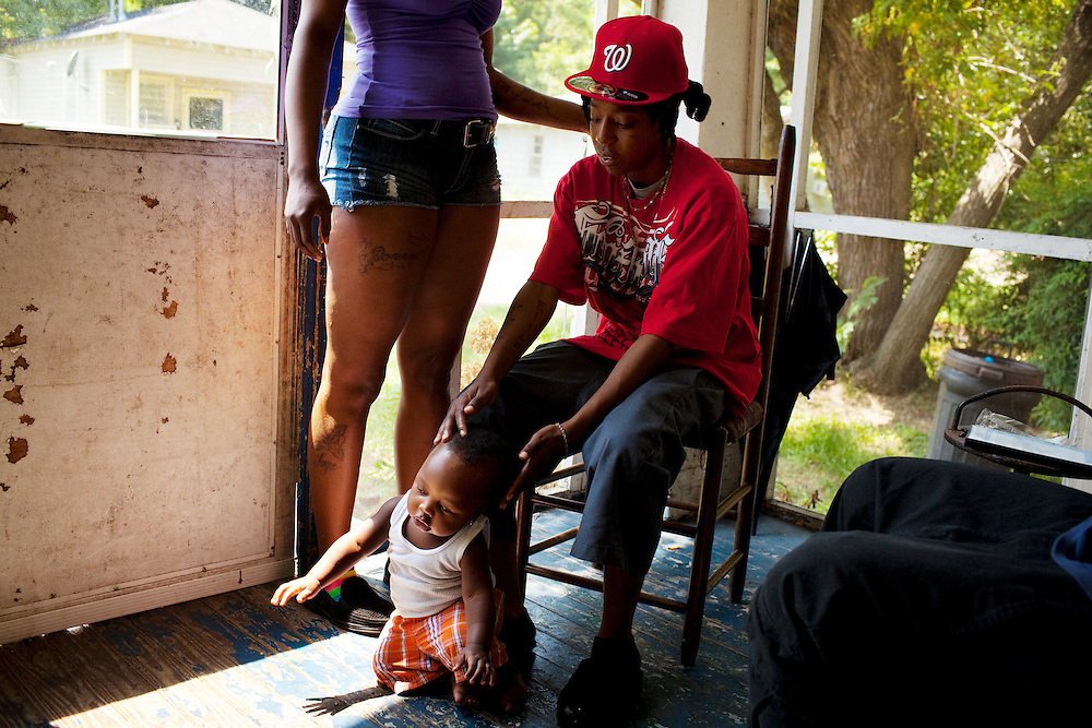 """Nikki Wilson tries to help """"Fat Man"""" takes early steps towards his mother's friend as they spend time together on a front porch on July 3, 2010 in Baptist Town, Mississippi."""