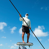 Buddy, a native Bahamian and our guide for the bone fishing trip, is standing on the platform of the boat keeping a look out for the fish. The water is very shallow, and we move silently with Buddy poling the boat through the water.