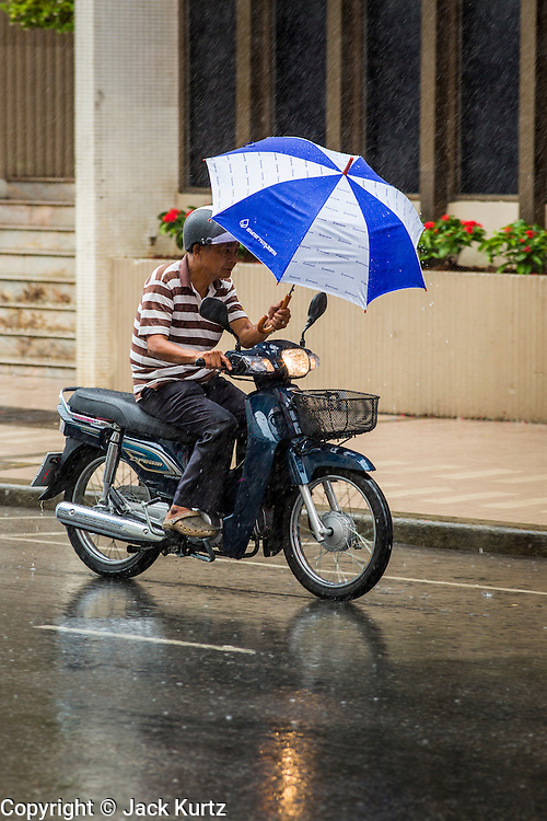 23 OCTOBER 2012 - HAT YAI, THAILAND:      Motor scooter riders use umbrellas to keep drive while drive through a rainy season storm in Hat Yai, Thailand. Hat Yai is the largest in southern Thailand. It is an important commercial center and tourist destination. It is especially popular with Malaysian, Singaporean and Chinese tourists.        PHOTO BY JACK KURTZ