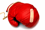Red boxing glove with band aid on a white background