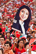 01 JULY 2011 - BANGKOK, THAILAND:  A man holds a placard showing a likeness of Yingluck Shinawatra, the Pheua Thai candidate for Prime Minister, during a Pheua Thai rally in Bangkok Friday. Thailand's divisive election campaign drew to a close Friday in Bangkok. Most of the parties had large rallies in an effort to sway last minute undecided voters. Pheua Thai, the party of ousted Prime Minister Thaksin Shinawatra held a massive rally in Rajamakala Stadium (also called Ramkamhaeng Stadium) to close out their campaign. A monsoon thunderstorm didn't keep people away from the event. Most Thai public opinion polls show Pheua Thai with a healthy lead over their arch rivals (and incumbent party in power) the Democrats. Thaksin's youngest sister, Yingluck Shinawatra, is running for Prime Minister under the Pheua Thai banner. If elected, she will be Thailand's first female Prime Minister.      PHOTO BY JACK KURT