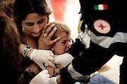ROMA. UNA MADRE TIENE FERMO IL CAPO DI SUO FIGLIO MENTRE I MEDICI DELLA CROCE ROSSA ITALIANA INIETTANO IL VACCINO.
