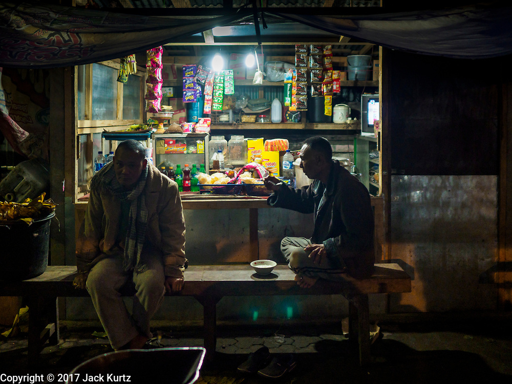 04 AUGUST 2017 - PAYANGAN, BALI, INDONESIA: Men get breakfast before sunrise in the local market in Payangan, about 45 minutes from Ubud. Bali's local markets are open on an every three day rotating schedule because venders travel from town to town. Before modern refrigeration and convenience stores became common place on Bali, markets were thriving community gatherings. Fewer people shop at markets now as more and more consumers go to convenience stores and more families have refrigerators.      PHOTO BY JACK KURTZ