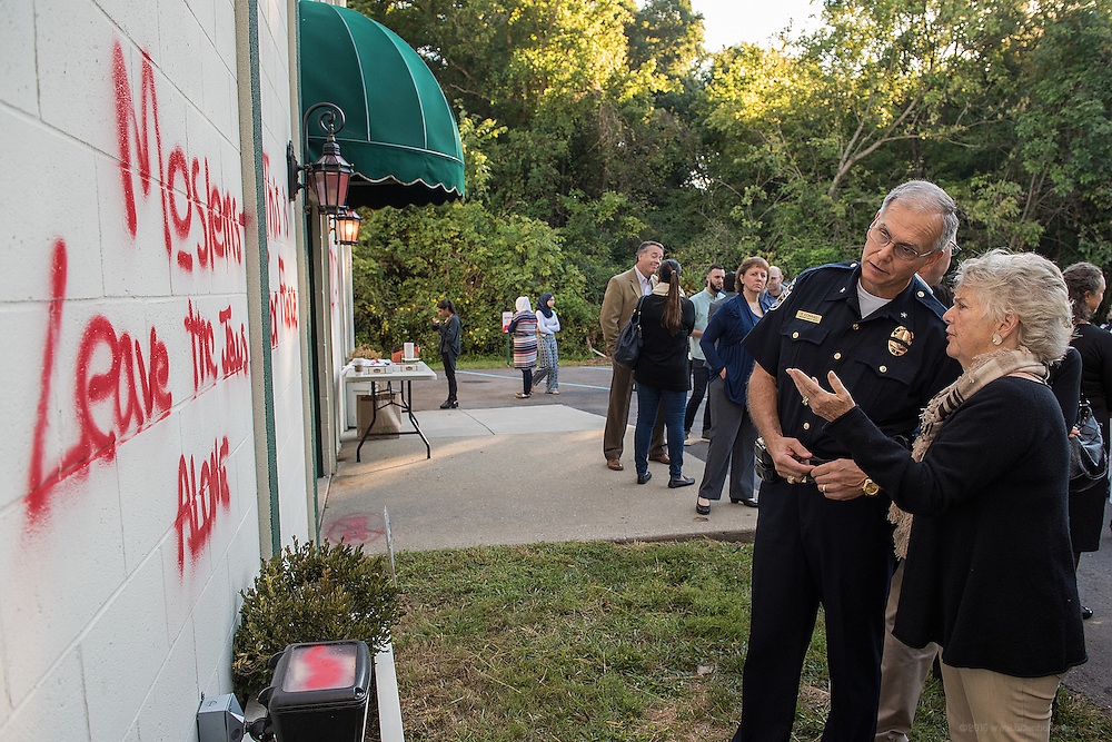 Christy Brown, founder of the Center for Interfaith Realtions and Police Chief Steve Conrad talk as they look at graffiti sprayed on the Louisville Islamic Center on River Road Wednesday night. Sep. 17, 2015