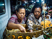 11 OCTOBER 2016 - UBUD, BALI, INDONESIA: Women shop for marigold garlands in the market in Ubud. The morning market in Ubud is for produce and meat and serves local people from about 4:30 AM until about 7:30 AM. As the morning progresses the local vendors pack up and leave and vendors selling tourist curios move in. By about 8:30 AM the market is mostly a tourist market selling curios to tourists. Ubud is Bali's art and cultural center.      PHOTO BY JACK KURTZ