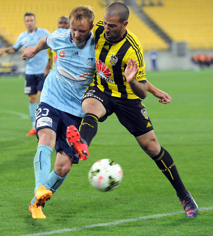 Sydney FC's Rhyan Grant, left clashes with Phoenix's Manny Muscat in the A-League football match at Westpac Stadium, Wellington, New Zealand, Sunday, April 26, 2015. Credit:SNPA / Ross Setford