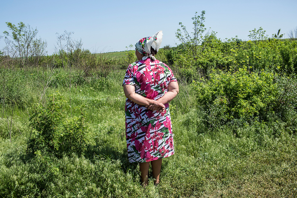 STAROVARVAROVKA, UKRAINE - MAY 16:  A woman looks off into a field at the funeral of Elena Ott, 42, on May 16, 2014 in Starovarvarovka, Ukraine. Ott was killed two days prior when the car she was riding in was fired on by forces her family believes to be the Ukrainian military. (Photo by Brendan Hoffman/Getty Images) *** Local Caption ***