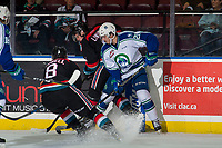 KELOWNA, CANADA - OCTOBER 23: Owen Blocker #21 of the Swift Current Broncos checks Mark Liwiski #9 into the boards as Jack Cowell #8 of the Kelowna Rockets digs for the puck during second period on October 23, 2018 at Prospera Place in Kelowna, British Columbia, Canada.  (Photo by Marissa Baecker/Shoot the Breeze)