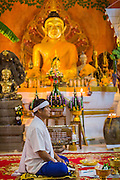 "29 JUNE 2014 - DAN SAI, LOEI, THAILAND:  A man meditates in Wat Ponchai during the ""Ghost Festival."" Phi Ta Khon (also spelled Pee Ta Khon) is the Ghost Festival. Over three days, the town's residents invite protection from Phra U-pakut, the spirit that lives in the Mun River, which runs through Dan Sai. People in the town and surrounding villages wear costumes made of patchwork and ornate masks and are thought be ghosts who were awoken from the dead when Vessantra Jataka (one of the Buddhas) came out of the forest. On the last day of the festival people participate in merit making ceremonies at the Wat Ponchai in Dan Sai and lead processions through town soliciting donations for the temple.    PHOTO BY JACK KURTZ"