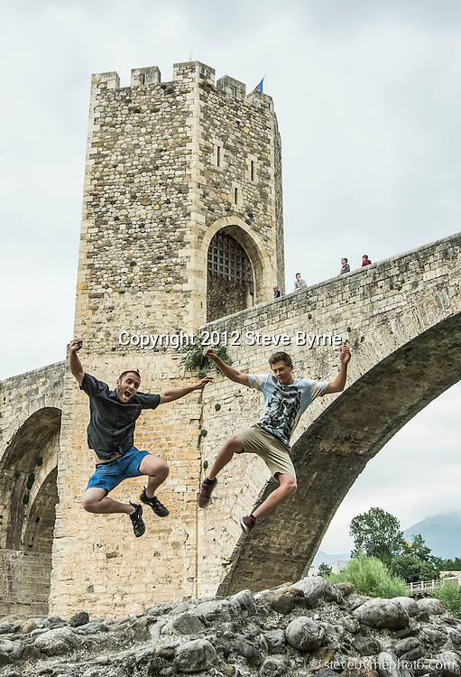 Teacher and student heel click beneath Besalu's iconic bridge.