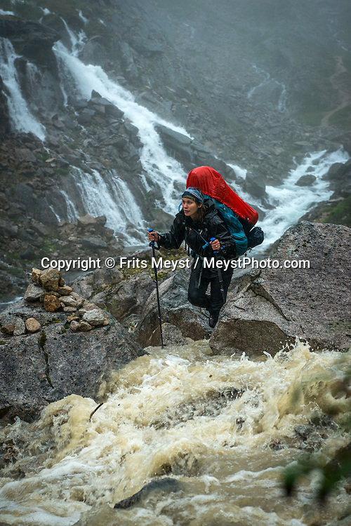 Alaska, USA to Yukon Territory, Canada, September 2014. A hiker crosses the swollen mountain creeks during torrential rain on the way to the Chilkoot Pass.  Starting at Dyea, Alaska, The Chilkoot Trail retraces the Klondike Gold Rush route that most stampeders followed to get to the gold fields. Steeped in Klondike Gold Rush history and scattered with relics from the past, the famous Chilkoot Trail is also referred to as the longest open air museum in the world. This rugged 55 kilometer wilderness trek is a world-renowned hiking trail and Canada's largest National Historic Site. Photo by Frits Meyst / MeystPhoto.com