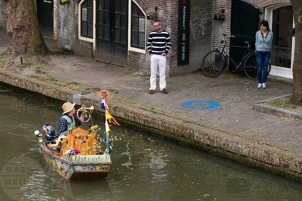 Muzikant Reinier Sijpkens vaart met zijn muziekboot Notendop door de Oudegracht in Utrecht.<br /> <br /> Musician Reinier Sijpkens sails with his so called music boat Notendop in the canals of Utrecht.