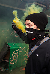 © Licensed to London News Pictures . FILE PHOTO DATED 26/03/2011 of a Black Bloc protester with a flare at a demonstration in London as reports circulate that black bloc tactics may be employed by protesters seeking to demonstrate during the funeral of former British Prime Minister Margaret Thatcher . Photo credit : Joel Goodman/LNP