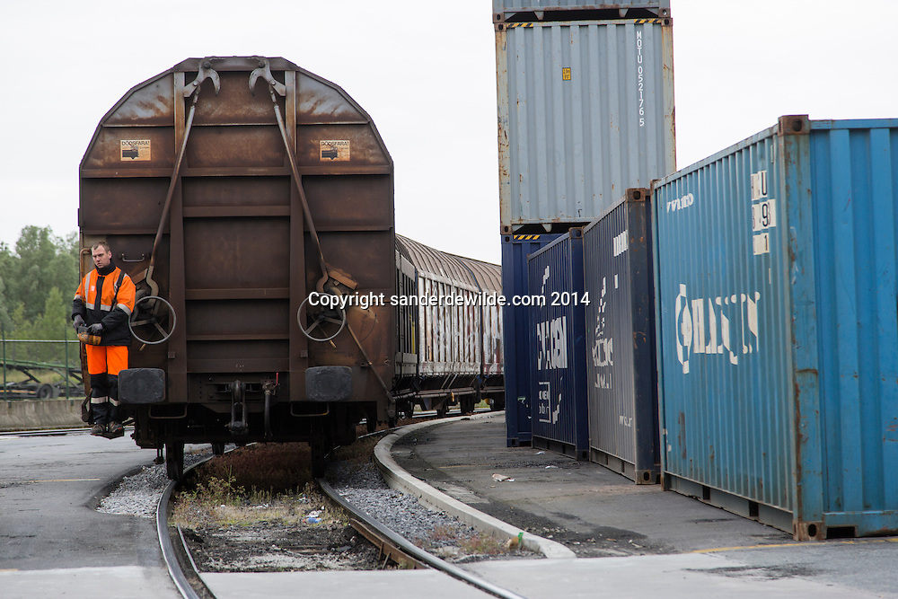 A train passing by containters at van moer rail services in the port of antwerp driven by a guy in front of the train