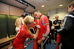 CARDIFF, WALES - Tuesday, October 13, 2015: Wales' Jonathan Williams signs Hal Robson-Kanu's shirt in the dressing room after the 2-0 victory over Andorra, and qualification for the finals, following the UEFA Euro 2016 qualifying Group B match at the Cardiff City Stadium. (Pic by David Rawcliffe/Propaganda)