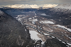 This aerial photo of the upper Chilkat River valley taken above Mosquito Lake shows the upper portion of the Alaska Chilkat Bald Eagle Preserve. At upper left is the Kelsall River valley. Identifiable mountains include: Hiteshitak Mountain (left of center), Tohikah Mountain (center), and Mount Raymond (rear right in sunlight area). During late fall, bald eagles congregate along the Chilkat River to feed on salmon. This gathering of bald eagles in the Alaska Chilkat Bald Eagle Preserve is believed to be one of the largest gatherings of bald eagles in the world.