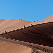 Hikers at Sossusvlei sand dunes in Namibia.