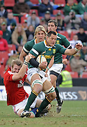 Pierre Spies of the Springboks on the charge with Tom Croft of the Lions hanging on for dear life. In support is Wynand Olivier and Ruan Pienaar of the Springboks. <br /> Rugby - 090704 - Springboks vs British&Irish Lions - Coca-Cola Park - Johannesburg - South Africa. The Lions won the third test 28-9 but lost the series 2-1 to the Springboks.<br /> Photographer : Anton de Villiers / SASPA
