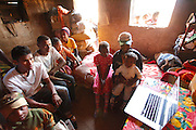 Sidonie with her parents and extended family watch a slideshow of Sidonie's experience during surgery. <br /> Follow up visit to see Sidonie Haritiana (Patient No 074) who received surgery for her Unilateral Cleft Lip during Operation Smile&rsquo;s 2011 mission to Antananarivo when she was 7 years old. <br /> <br /> Sidonie is now 9 years old and lives with her Father Patrick, Mother Harinirima, Older Sister Chantale and younger sister Jafia. In a one room hut they rent near the brickworks which her mother and father work in. Sidonie attends school but as she is on summer holidays she helps her mother and father at work in the brick works.<br /> <br /> Outskirts of Antananarivo. Madagascar. 25th August 2014.<br /> <br /> (Operation Smile Photo - Zute Lightfoot)