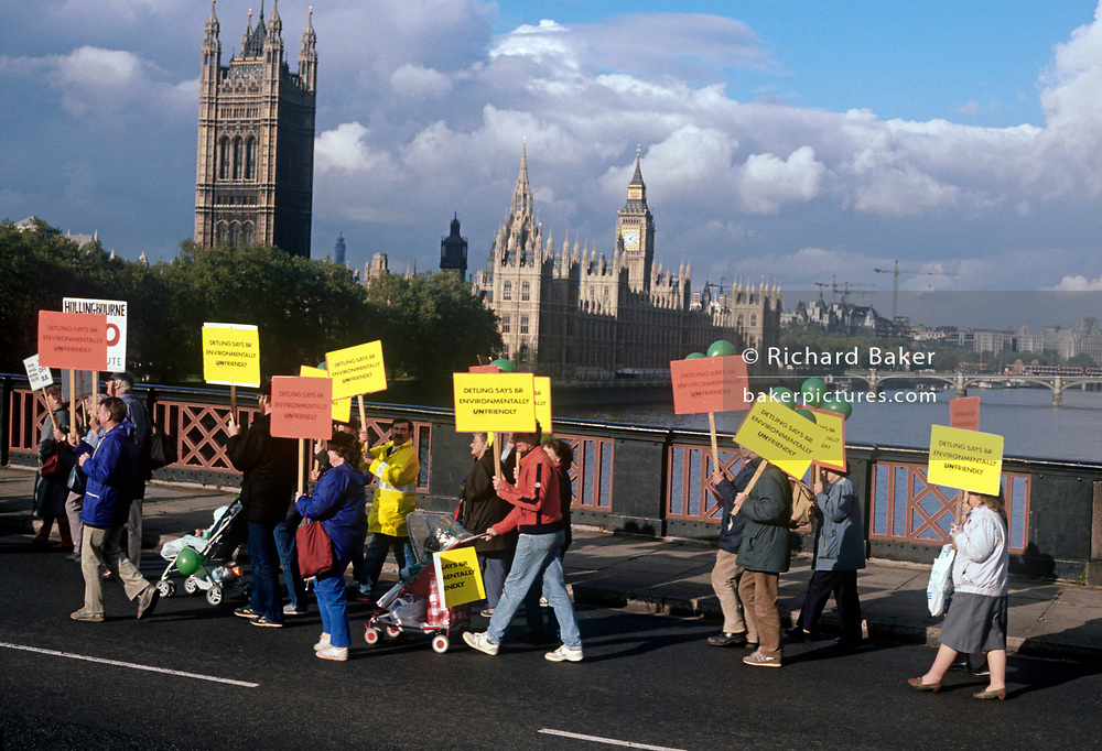 Angry residents from Kent march over the river Thames and past Parliament to protest over the planned high-speed (TGV-style) rail link from London to the south-east coast, on 5th August 1989, in London, England. Locals from the Darenth Valley in rural Kent, against the forthcoming Channel Tunnel rail link organised their own campaign to reverse decisions by British Rail to cut a new rail link through their community. British Rail announced that 150mph TGV trains would travel through their rural Kent countryside, forcing residents to sell their homes within a 240 metre corridor to the rail line, at great loss while splitting up the community. (Photo by Richard Baker / In Pictures via Getty Images)