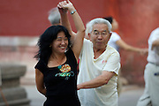 Jingshan (Coal Hill) Park. Elderly man and young woman shaking it during a morning dance lesson.