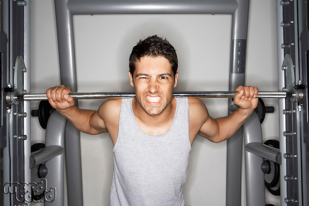 Man Grimacing while Lifting Weights on weight machine portrait