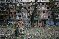 Local woman passes damaged block of flats after Ukranian army shelling downtown of Khartsyzk (24km from Donetsk), Ukraine, 18 August 2014. Within a few weeks  the Ukrainian army continues shelling the living suburbs of Donetsk hundreds of homes destroyed more than half the city's population had fled their homes. At night the damaged power line supply pumping station feeding drinking water to the city of more than 500 thousand remaining residents do not have access to water.