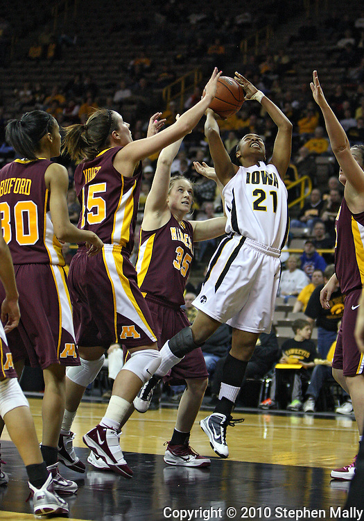 February 18, 2010: Iowa guard Kachine Alexander (21) puts up a shot while surrounded by Minnesota defenders during the first half of the NCAA women's basketball game at Carver-Hawkeye Arena in Iowa City, Iowa on February 18, 2010. Iowa defeated Minnesota 75-54.