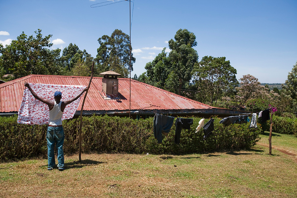 Kibet Serem hangs up laundry that he has just washed.  (Kibet Serem is featured in the book What I Eat: Around the World in 80 Diets. He is 25 years of age.) He cares for a small tea plantation that his father planted on their property near Kericho, Kenya when Kibet was a young boy and he is responsible for milking the cows that his family owns. He is 25 years of age. He sells extra milk to a nearby school for a government feeding program and gives some to his mother who makes yogurt and sells it.