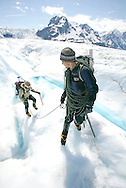 Two winter hikers cross a glacier field roped up with climbing gear and majestic mountains covered with snow in the background.