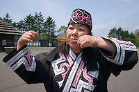 An Ainu women elder plays a traditional stringed instrument - the Mukkur.