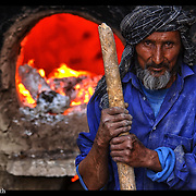 An Afghanistan brickmaker attends to his makeshift factory near Kabul, Afghanistan, on Aug. 27, 2002.