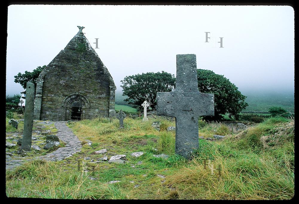 Crude stone cross & Ogham stone frame Romanesque Kilmalkedar Church (12th-c);Dingle Peninsula Ireland