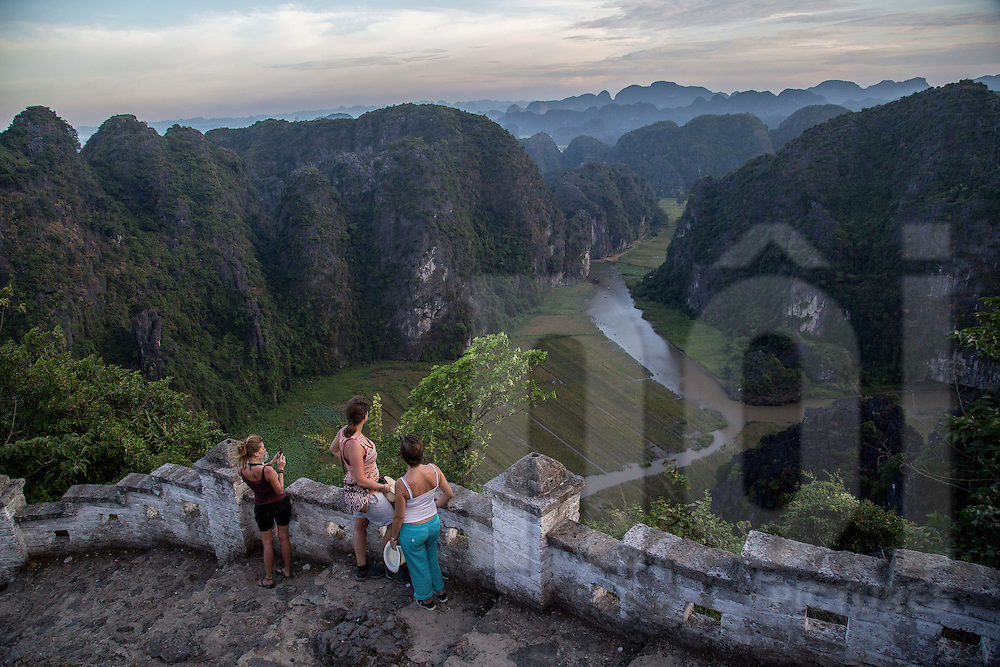 A group of caucasian girls on top of Ngu Nhac Mountain overlook outstanding landscape of Tam Coc and karstic rock formations, Ninh Binh, Vietnam, Southeast Asia