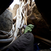 April 28, 2012 - Tabania, Nuba Mountains, South Kordofan, Sudan: A Nuba woman takes cover, from possible bombardments by Sudan's Army Forces airplane, in some caves near Buram village. Since the 6th of June 2011, the Sudan's Army Forces (SAF) initiated, under direct orders from President Bashir, an attack campaign against civil areas throughout the South Kordofan's province. Hundreds have been killed and many more injured...Local residents, of Nuba origin, have since lived in fear and the majority moved from their homes to caves in the nearby mountains. Others chose to find refuge in South Sudan, driven by the lack of food cause by the agriculture production halt due to the constant bombardments of rural areas.
