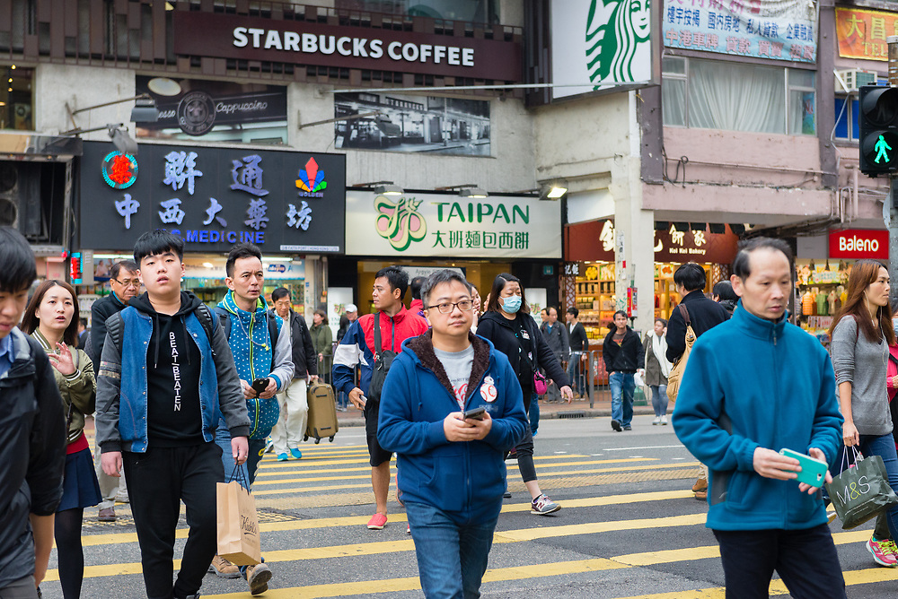 Pedestrians crossing a busy street in Kowloon, Hong Kong