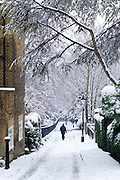 Lone figure walks through deep snow in Holly Place in leafy Hampstead, North London, United Kingdom