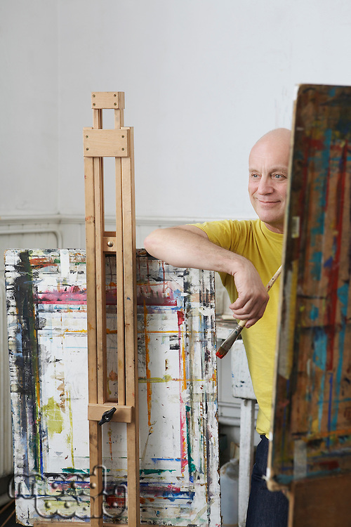 Relaxed male artist with paint brush leaning against easel