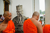 Buddhist monks walk by a traditional statue at temple Wat Pho, Bangkok, Thailand