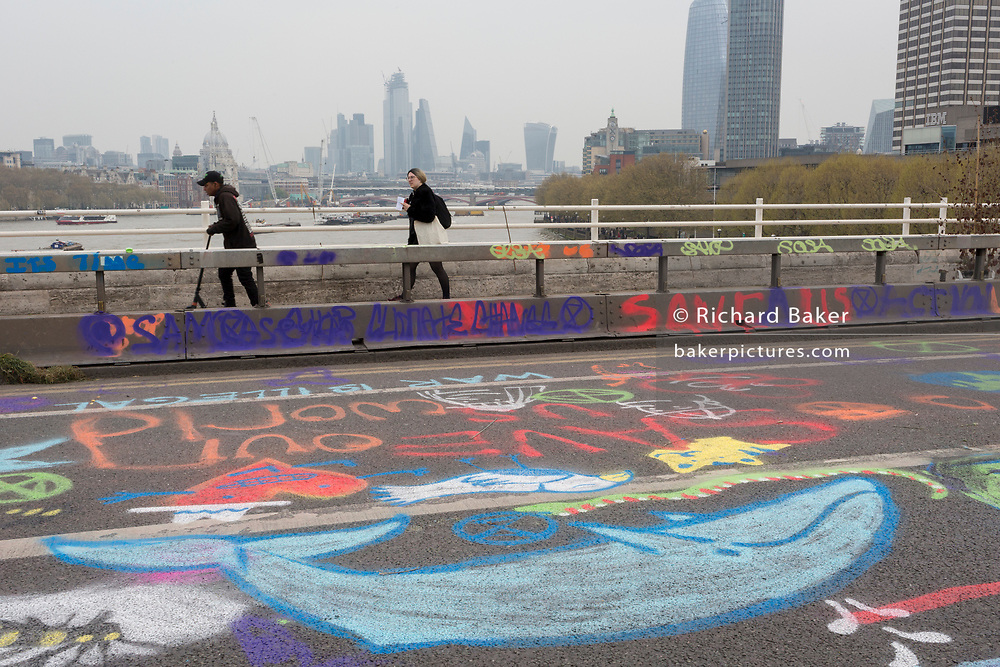 Pedestrians walk over Waterloo Bridge while Climate Change activists with Extinction Rebellion campaign for a better future for planet Earth after blocking Waterloo Bridge and as part of a multi-location 5-day Easter protest around the capital, on 16th April 2019, in London, England.