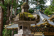 """Old Japanese lantern. Toshogu Shrine is the final resting place of Tokugawa Ieyasu, the founder of the Tokugawa Shogunate that ruled Japan for over 250 years until 1868. Ieyasu is enshrined at Toshogu as the deity Tosho Daigongen, """"Great Deity of the East Shining Light"""". Initially a relatively simple mausoleum, Toshogu was enlarged into the spectacular complex seen today by Ieyasu's grandson Iemitsu during the first half of the 1600s. The lavishly decorated shrine complex consists of more than a dozen buildings set in a beautiful forest. Countless wood carvings and large amounts of gold leaf were used to decorate the buildings in a way not seen elsewhere in Japan. Toshogu contains both Shinto and Buddhist elements, as was common until the Meiji Period when Shinto was deliberately separated from Buddhism. Toshogu is part of Shrines and Temples of Nikko UNESCO World Heritage site."""