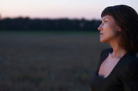 Woman stands in a field at twilight