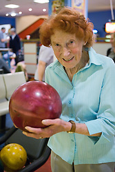 Portrait of an Elderly woman holding ten pin bowling ball,