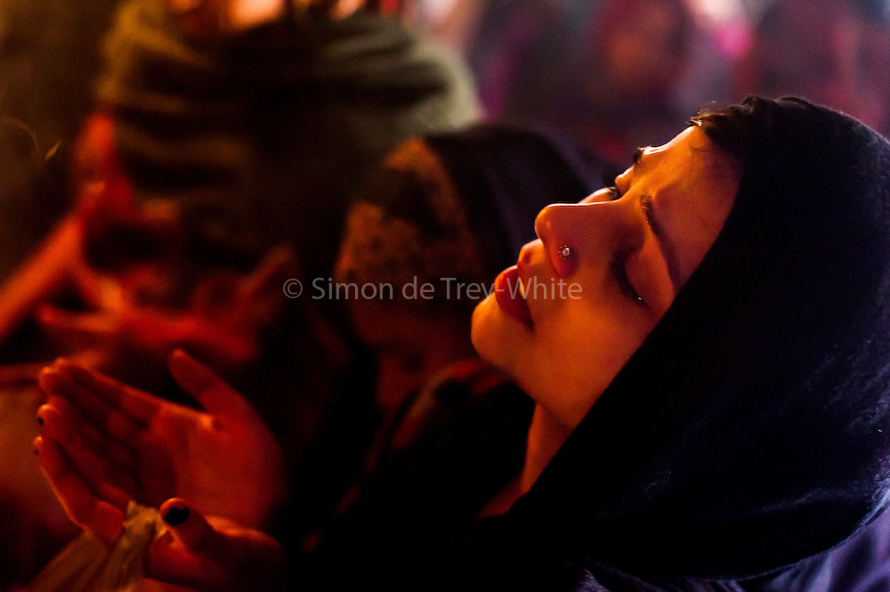 4th December 2014, New Delhi, India. A Muslim woman prays for her wishes to be granted by Djinns in the ruins of Feroz Shah Kotla in New Delhi, India on the 4th December 2014<br /> <br /> PHOTOGRAPH BY AND COPYRIGHT OF SIMON DE TREY-WHITE a photographer in delhi<br /> + 91 98103 99809. Email: simon@simondetreywhite.com<br /> <br /> People have been coming to Firoz Shah Kotla to leave written notes and offerings for Djinns in the hopes of getting wishes granted since the late 1970's. <br /> Feroz Shah Tughlaq (r. 1351&ndash;88), the Sultan of Delhi, established the fortified city of Ferozabad in 1354, as the new capital of the Delhi Sultanate, and included in it the site of the present Feroz Shah Kotla. Kotla literally means fortress or citadel. The pillar, also called obelisk or Lat is an Ashoka Column, attributed to Mauryan ruler Ashoka. The 13.1 metres high column, made of polished sandstone and dating from the 3rd Century BC, was brought from Ambala in 14th century AD under orders of Feroz Shah. It was installed on a three-tiered arcaded pavilion near the congregational mosque, inside the Sultanate's fort. In centuries that followed, much of the structure and buildings near it were destroyed as subsequent rulers dismantled them and reused the spolia as building materials.